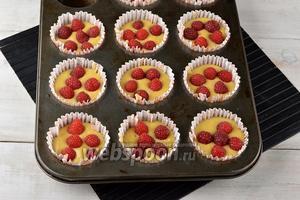 В форму для приготовления выложить бумажные формочки. Заполнить их тестом на 2/3. Сверху разложить ягоды малины (150 г).