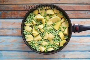 Картофель (300 г) очистить, нарезать крупными кусочками. Выложить в сковороду или другую жаропрочную форму для запекания. Выложить замороженный зелёный горошек (100 г, можно и свежий). Посолить и поперчить по вкусу.