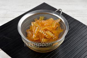 Вынуть арбузные корки из кастрюли, поместить в сито и дать полностью стечь сиропу.