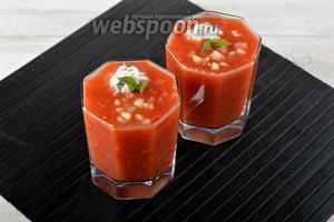 Разлить охлаждённый гаспачо по стаканам или тарелкам. Сверху выложить кубики огурцов, арбуза, перца, а также шарик из Феты и укропа. Украсить мятой.
