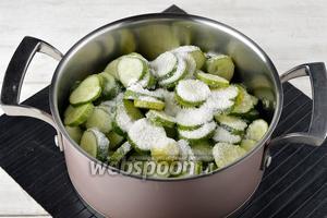 В кастрюле соединить огурцы, лук. Посыпать солью (3 ст. л.) и тщательно перемешать.