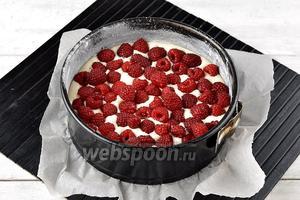 Форму (диаметром 18 сантиметров) выложить кулинарной бумагой. Смазать форму сливочным маслом (1 ст. л.) и присыпать мукой (1 ст. л.). Выложить в форму 2/3 части теста, а сверху разложить ягоды малины (1 стакан).