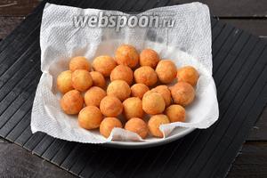 Вынуть каждую порцию обжаренных шариков с помощью шумовки и выложить на бумажные салфетки, для того, чтобы удалить лишний жир.