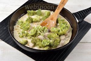 Вернуть в сковороду к луку куриное филе. Брокколи (300 г) промыть, очистить, разделить на соцветия и удалить толстые «ножки». Выложить соцветия брокколи в сковороду. Добавить сливки (250 мл). Перемешать.