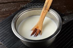 В толстостенную кастрюлю поместить молоко (700 мл), сахар (50 г) и корицу (2 палочки).