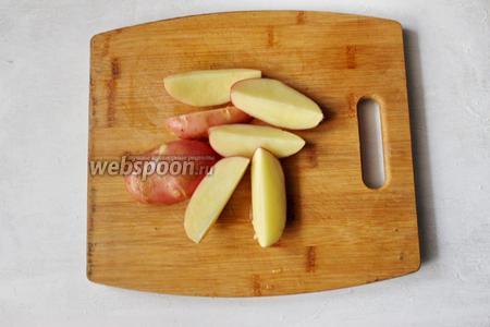 Включим духовку на 200°С. Картофель хорошо помоем. Затем разрежем его на 4 части.
