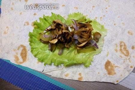 На лаваш кладем лист салата, на него выдавим небольшую полоску майонеза. Дальше кладём нашинкованные лук и огурец, и обжаренные грибы.