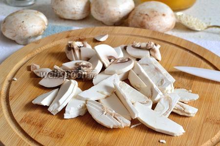 Затем чистим шампиньоны и режем тонкими ломтиками. Ломтики крупных грибов можно разрезать ещё пополам.