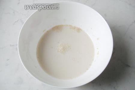 В миску налить молоко и воду, подогреть до 35-40°С. Добавить дрожжи и сахар. Дать постоять 10-15 минут,  вскоре дрожжи начнут пениться.