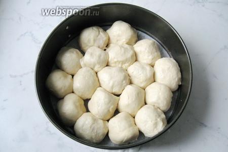 В форму для выпечки выложить шарики с сосисками, швом вниз.