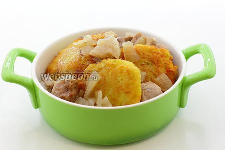 Запекать можно порционно или в одной форме. В формочку уложите драники. Добавьте обжаренную свинину. Налейте мясной бульон до половины формочки. Отправьте в горячую духовку (180°C). Запекайте 30-40 минут.