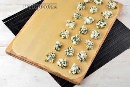 Выложить на тесто по 1 чайной ложке начинки, отступая каждый раз 3-3,5 сантиметра.
