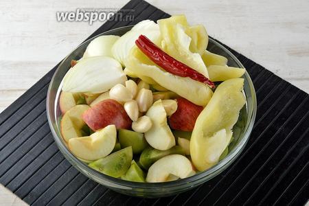Овощи подготовить к переработке: вымыть помидоры, яблоки и перцы. Помидоры (800 г) разрезать на 4 части. 3 сладких перца и 1 острый перец очистить от семян. Лук (1 шт.) и чеснок (1 головку) очистить. Лук разрезать на 6-8 частей. У 2 яблок удалить сердцевину и разрезать на дольки.