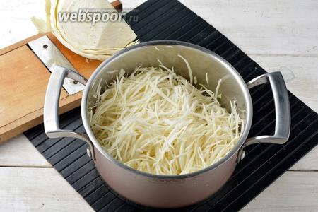 Первым делом следует пропарить капусту. Капусту (400 г) нашинковать очень тонко и выложить в кастрюлю вместе с водой (150 мл), посыпав солью (1 ч. л.).