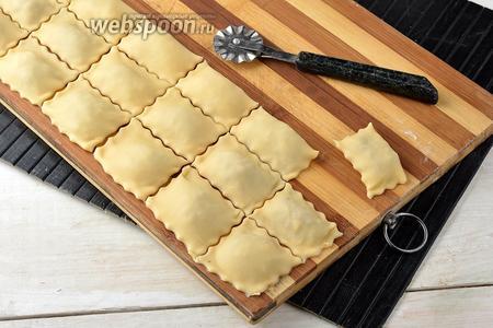 Накрыть второй частью теста. Пройтись пальцами вокруг  каждой порции начинки, выгоняя воздух и соединяя тесто. Разрезать тесто на равиоли с помощью специального колесика или обычным ножом. Проверить, плотно ли соединены пласты теста у каждой равиоли.