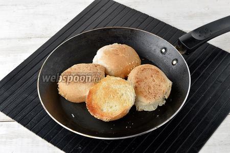 На сухой горячей сковороде подсушить разрезанные пополам 2 булочки.