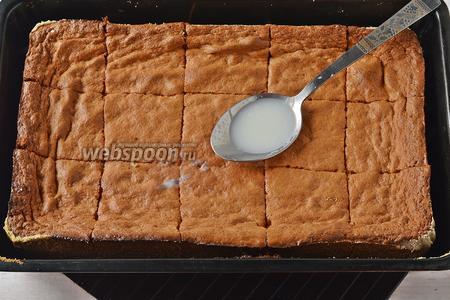 Готовый пирог вынуть из духовки и горячим разрезать ножом на порционные куски. Параллельно приготовить заливку: нагреть молоко (500 мл) с сахаром (3 ст. л.) и ванильным сахаром (10 г) до кипения и залить пирог этой горячей заливкой. Дать жидкости полностью впитаться. Отправить кох в холодильник на 1-2 часа.
