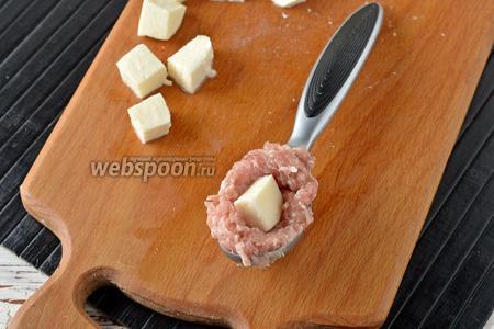 Сформировать мясные шарики с кубиком сыра внутри. Очень удобно для этого пользоваться небольшой ложкой для мороженого.