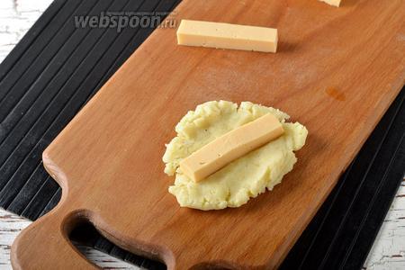 Отщипывать кусочек теста и формировать из него лепёшку. На центр лепёшки выложить брусок сыра.