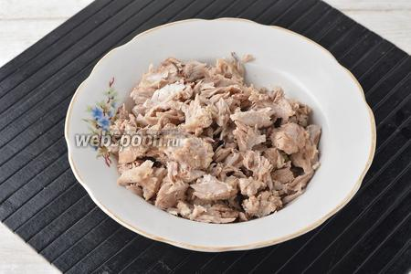 Из кастрюли вынуть рёбрышки. Отделить мясо от костей. Мясо порвать на небольшие кусочки. Вернуть мясо в кастрюлю.