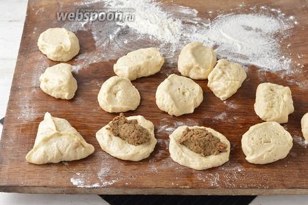 Тесто разделить на небольшие кусочки. Сформировать из каждого кусочка лепёшку. На середину лепёшки выложить 1 столовую ложку начинки. Сформировать пирожки.