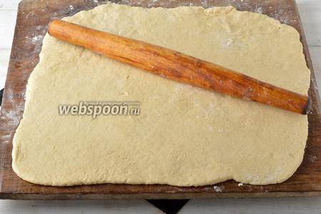 Вынуть тесто из холодильника и раскатать в прямоугольный пласт толщиной 0,5 см, на подпылённой мукой доске.