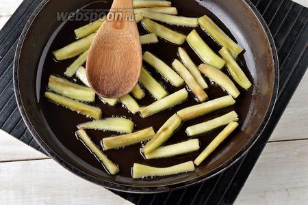 Затем промыть баклажаны. Обсушить и обжарить, помешивая, на горячей сковороде с подсолнечным маслом (2 ст. л.) до готовности (4-5 минут).