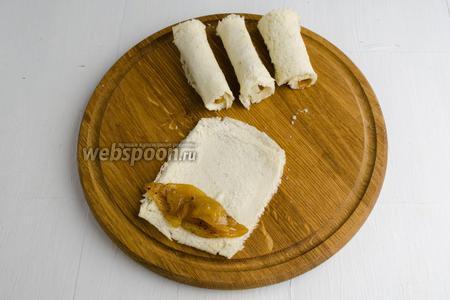 Выложить подготовленную яблочную начинку на край кусочка мякиша. Завернуть мякиш с начинкой в рулет.