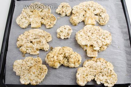 Разложить подготовленные доли капусты по пергаменту на противень. Запекать в режиме с обдувом до румяности, при температуре 180°С в течение 20 минут.