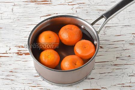 Мандарины тщательно вымыть в горячей воде (воспользуйтесь новой губкой), так как в рецепте будут использоваться мандарины вместе с кожурой. Выложить мандарины (400 г) в кастрюлю и залить их водой. Вода должна покрывать мандарины полностью. Из лимона выжать необходимое количество сока (1 ст. л.) и добавить в кастрюлю. Довести всё до кипения, убавить огонь до минимального и варить под крышкой 35 минут.