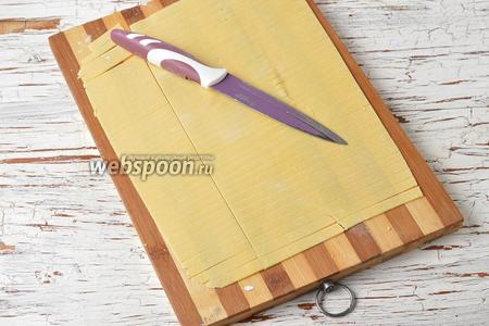 С помощью ножа разрезать тесто на полосочки в форме будущей лапши.