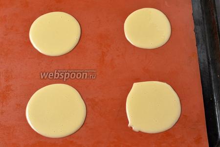 Духовку предварительно разогреть до 180°С. На силиконовый коврик наливать по 1 столовой ложке теста и размазывать его в круг. Оставляйте достаточно места между заготовками. Отправить противень с заготовками в духовку на 4-6 минут. Края теста должны стать золотистыми.