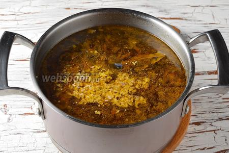 Проверить суп ещё раз на соль. Выложить в суп 1 лавровый лист. Снять кастрюлю с огня. Чеснок очистить, пропустить через пресс, выложить его в суп (2 зубчика). Накрыть кастрюлю крышкой и оставить на 5 минут.