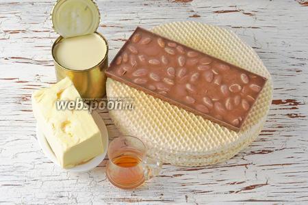 Для работы нам понадобится сливочное масло, сгущённое молоко, коньяк, вафельные коржи, молочный шоколад с целым миндалём.