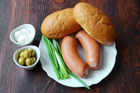 Для приготовления хот-дога с сарделькой вам понадобится лук зелёный, майонезно-чесночный соус, сардельки, булочки для хот-догов и оливки.
