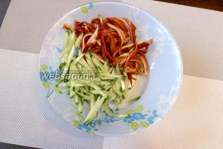 Огурец нарежем тонкой соломкой и добавим в салатник к уху.