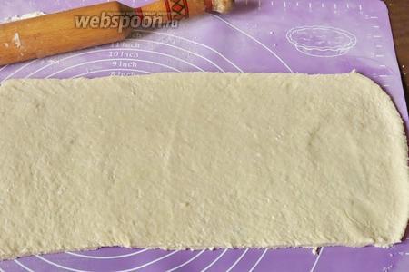 Раскатываем тесто прямоугольником, обильно присыпав поверхность мукой.