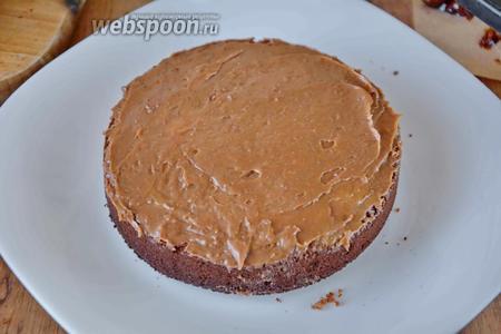 Сверху покрываем шоколадный слой бисквита кремом, равномерно распределяя его от центра к краям.
