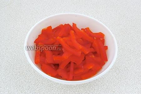 Стручки сладкого перца очистить от плодоножек и семяносцев с семенами, разрезать вдоль на 4 части, а затем каждую четвертинку нашинковать соломкой.