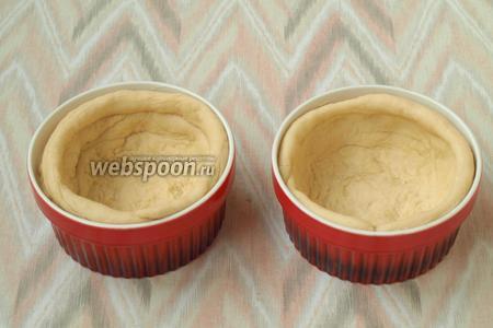 Формочки смазать сливочным маслом и выложить в каждую большую часть теста. Распластать тесто по формочке, делая бортики. Жгутиком выложить верх формочки.