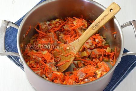 В толстостенную кастрюлю выложить масло, морковь, лук, свинину. Обжарить 1 минуту.