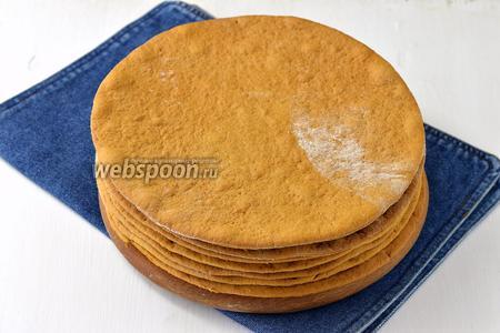 На посыпанном мукой столе раскатывать тонкие коржи. Вырезать ровные коржи и выпекать при температуре 180°С на присыпанном мукой противне 5-7 минут каждый корж.