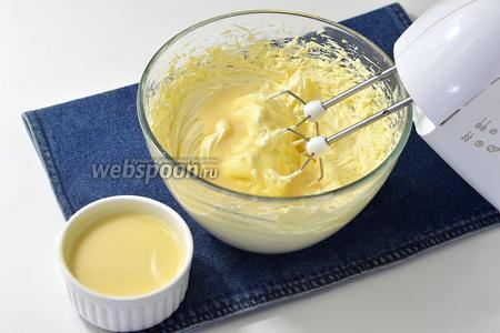 Порциями добавлять сгущённое молоко (125 г), постоянно взбивая.