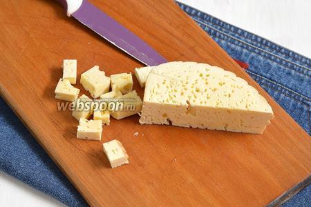 Брынзу (80 г) порезать квадратиками и разложить между овощей.