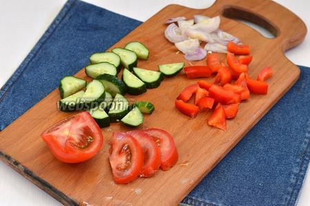 Все овощи вымыть и высушить. Лук (0,5 луковицы) очистить и нарезать полукольцами. Перец (0,5 перца) очистить от семян и нарезать кусочками. Помидоры (2 штуки) нарезать дольками, а огурцы (2 штуки) — крупными кусочками.