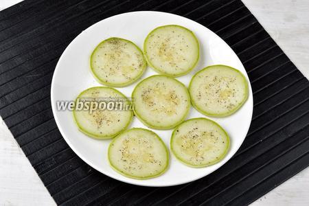 Разложить кабачковые колечки на тарелке так, чтобы они не заходили один на другой. Посыпать сверху солью (0,5 ч. л.) и любимыми специями.