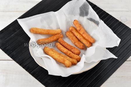 Вынуть палочки из кастрюли шумовкой и разложить на бумажных салфетках для того, чтобы впитался лишний жир.
