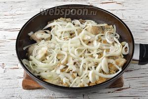 Перевернуть рыбу на другую сторону (в сковороде находится уже полная порция хека из двух обжарок), убавить огонь. Сверху на рыбу разложить очищенный и нарезанный полукольцами лук (1 штука). Приправить солью (1 ч. л.) и чёрным молотым перцем (0,1 ч. л.).