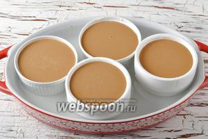 Небольшие жаропрочные формочки смазать сливочным маслом (1 ст. л.) и заполнить образованной смесью. Выложить формочки в глубокую форму, заполненную горячей водой.