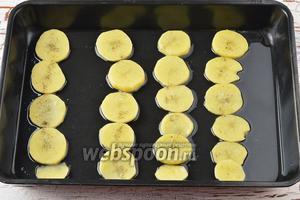 Тем временем очистить картофель (300 г) и нарезать тонкими кружочками. Форму обильно смазать подсолнечным маслом (4 ст. л.). На дно формы полосками выложить картофель, толщиной 4-5 миллиметров. Полосок картофеля должно быть столько, сколько у вас есть филешек рыбы. Посыпать картофель частью оставшейся соли и чёрного молотого перца.